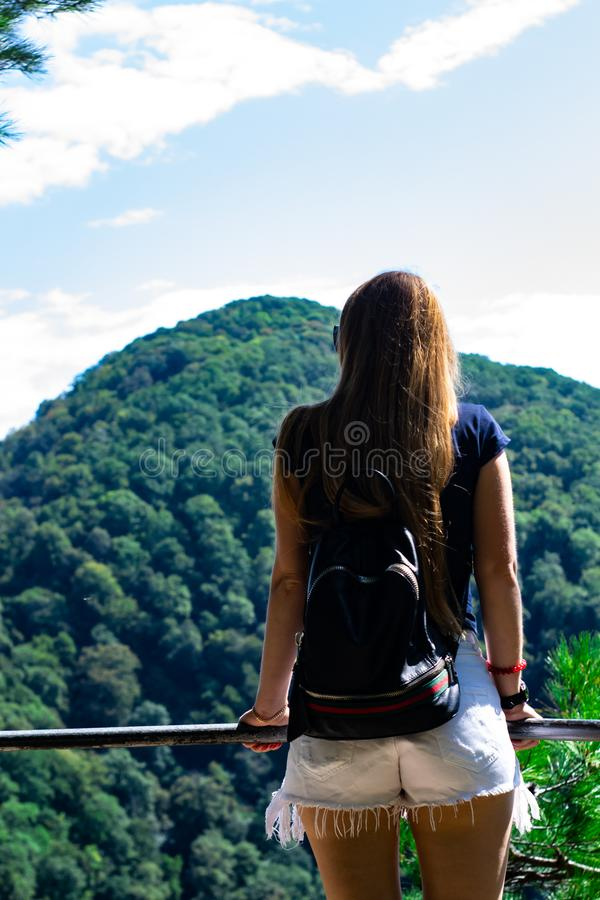 A lonely girl looks at the mountains on the other side. Low lying clouds and mountains.  royalty free stock photos
