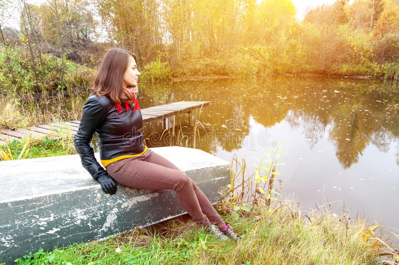 Lonely girl sitting on a boat on the lake royalty free stock photography