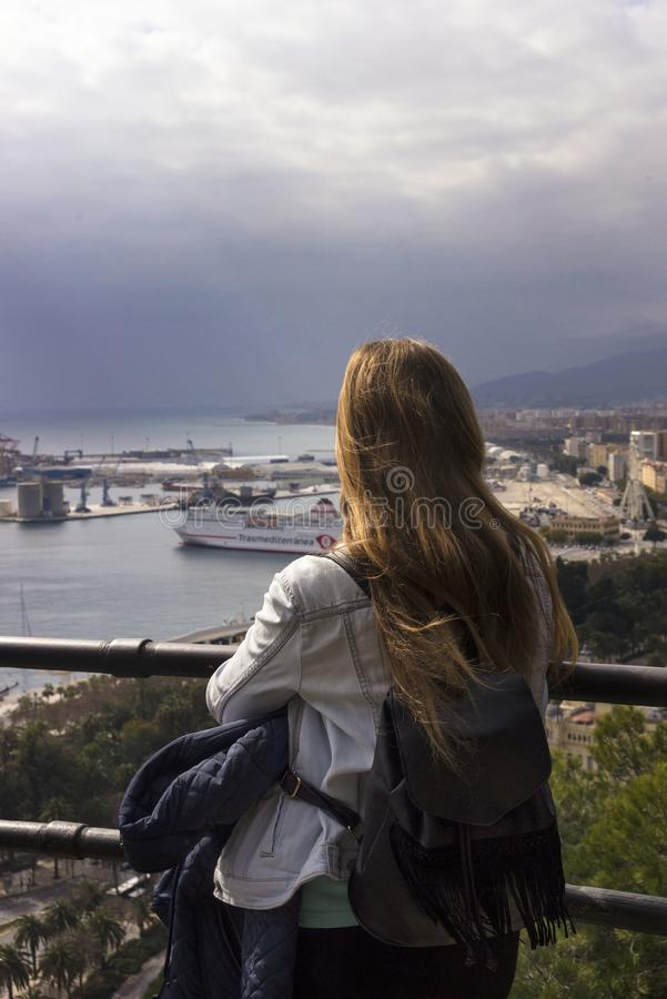 A lonely girl stands on a hill and looks at the beautiful panorama of the Spanish city of Malaga on a warm sunny day. royalty free stock images