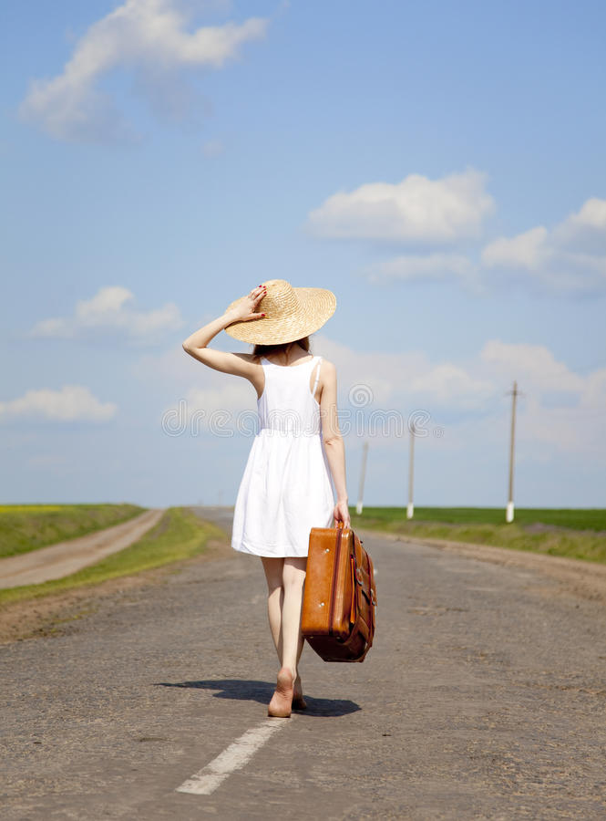 Lonely girl with suitcase at country road. royalty free stock photography