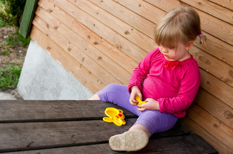 Lonely girl with toy. Lonely girl sat on wooden porch outdoors with toy stock images