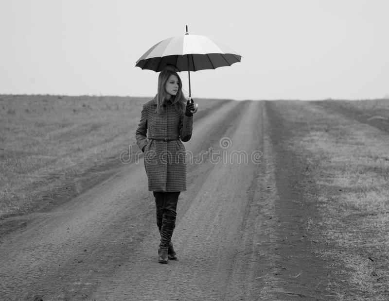 Lonely girl with umbrella at country road. stock photos