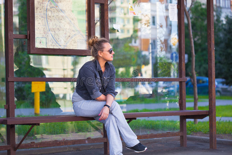 Lonely girl waiting for transport at the bus stop royalty free stock photography