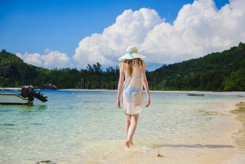 Lonely girl is walking along coastline royalty free stock image
