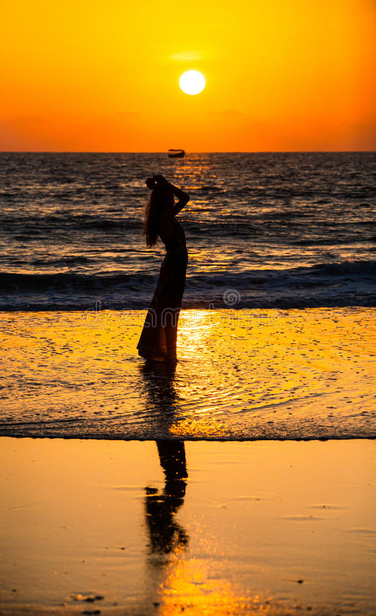 A lonely girl walking along island coastline and has reflection on wet sand. stock photos