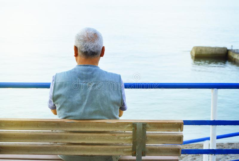 Lonely gray-haired elderly man sitting by the sea on a bench, a view from the back, contemplation of nature and a relaxing holiday. Lonely gray-haired elderly stock images