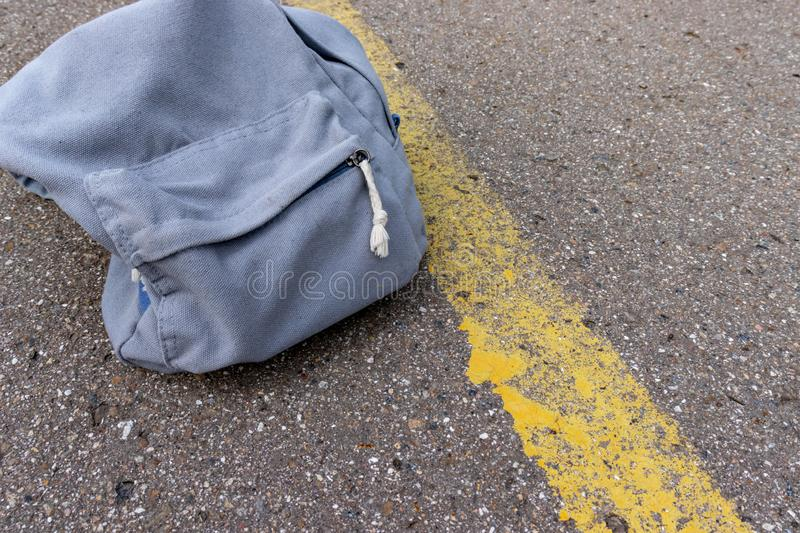 Lonely grey casual style backpack standing on asphalt road with yellow line road marking with copy space.  royalty free stock photo