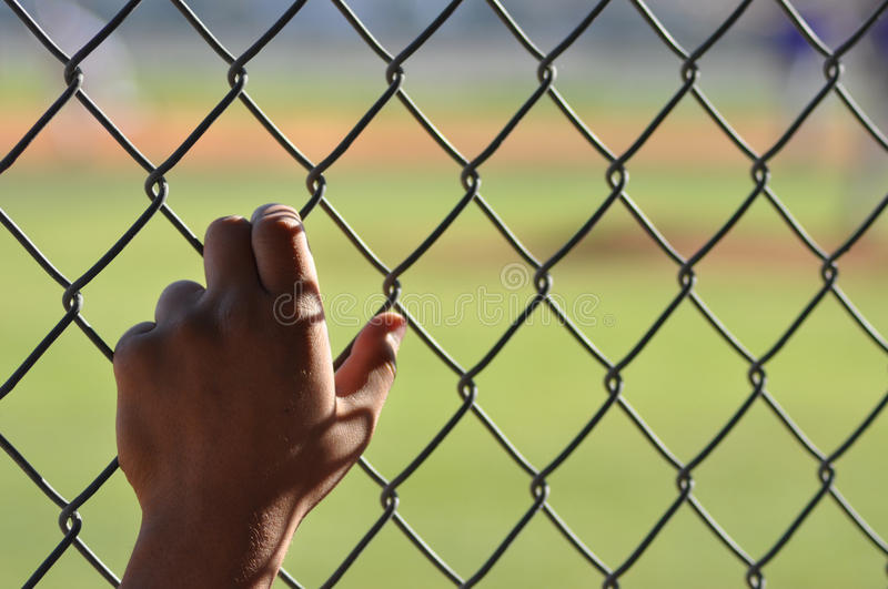 Lonely hand reaching out for help. One hand clutching chain link fence with a limited depth of field. It has natural light and was shot at a baseball field stock images