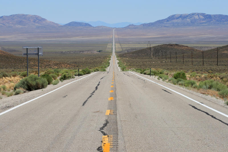 Lonely highway 6 in Nevada. Stretches across a wide valley in a straight line with heat ripples in the distance royalty free stock photo
