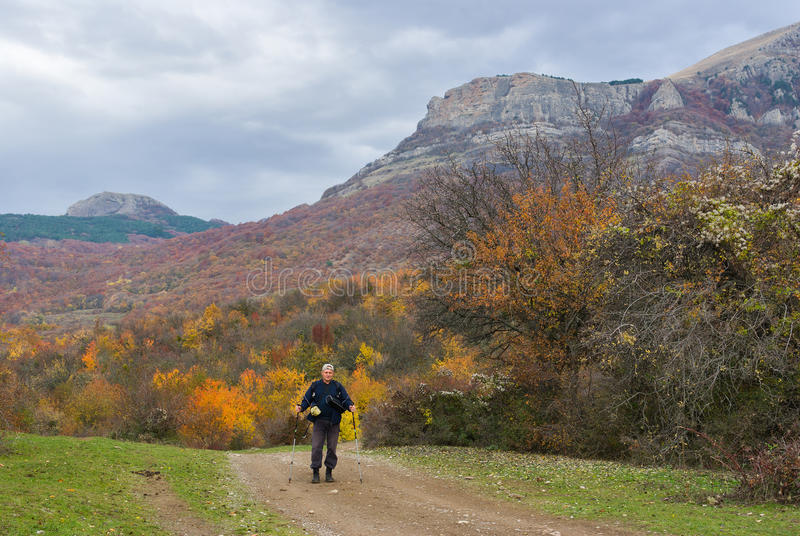 Lonely hiker on a mountain road royalty free stock photography