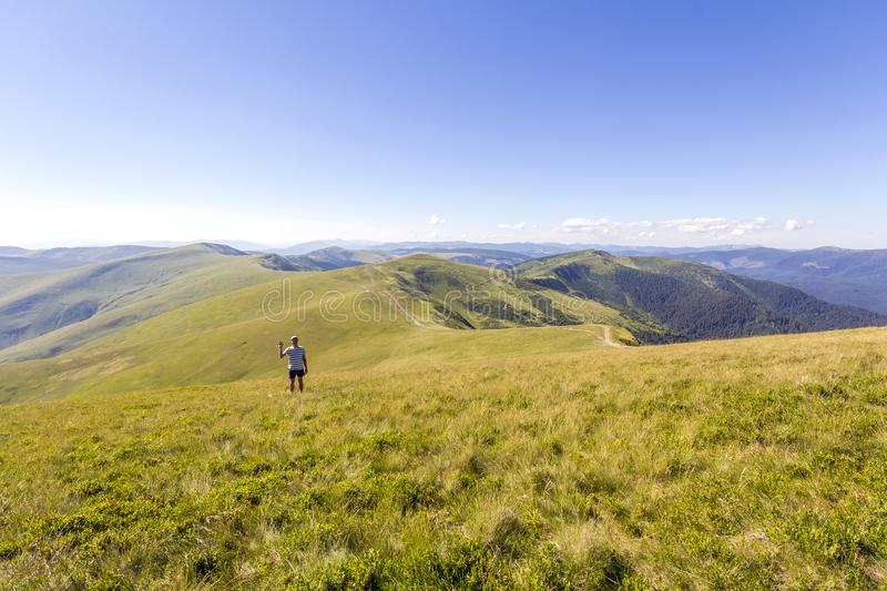 Lonely hiker standing in mountains. Tourist man enjoy mountain v stock images