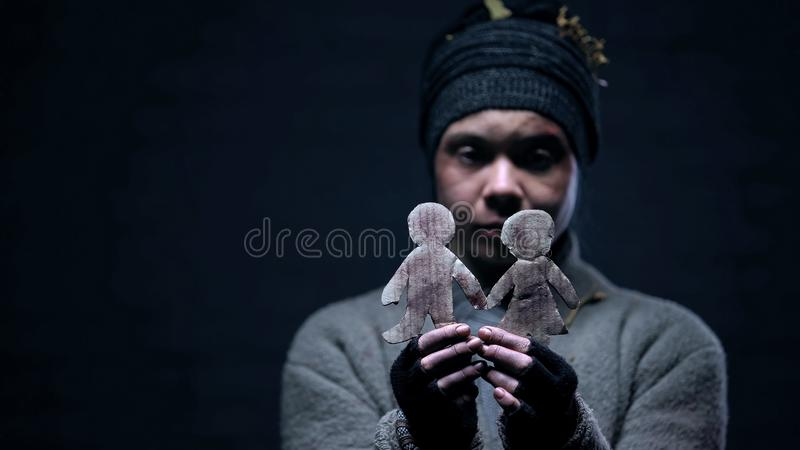 Lonely homeless female holding paper couple figure dreaming about happy family. Stock photo royalty free stock image