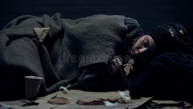 Lonely homeless person with paper figure lying on street missing home and family. Stock photo stock photos