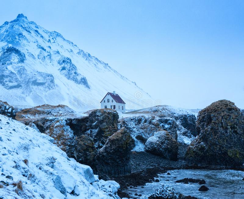 Lonely house behind cliffs near Arnarstapi village at dusk in winter, Snaefellsnes, Iceland.  royalty free stock image