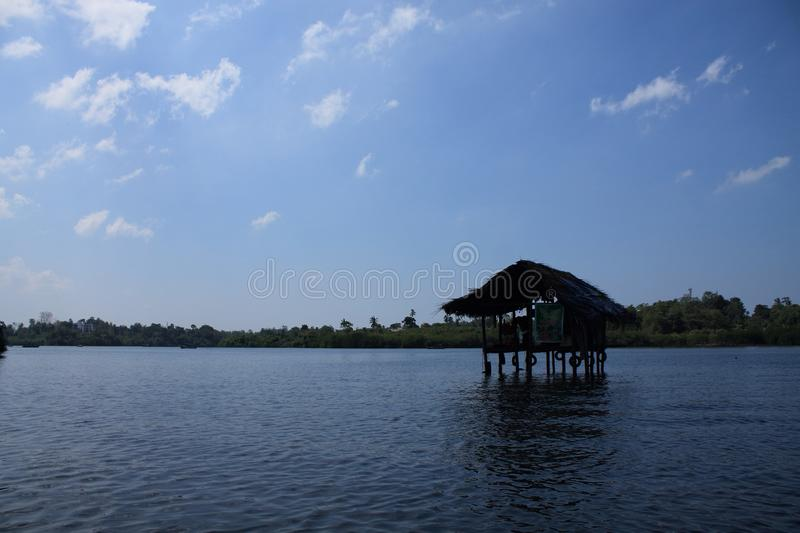 Lonely house on stilts in the river. Lonely straw house on stilts in the river. Blue sky royalty free stock photos
