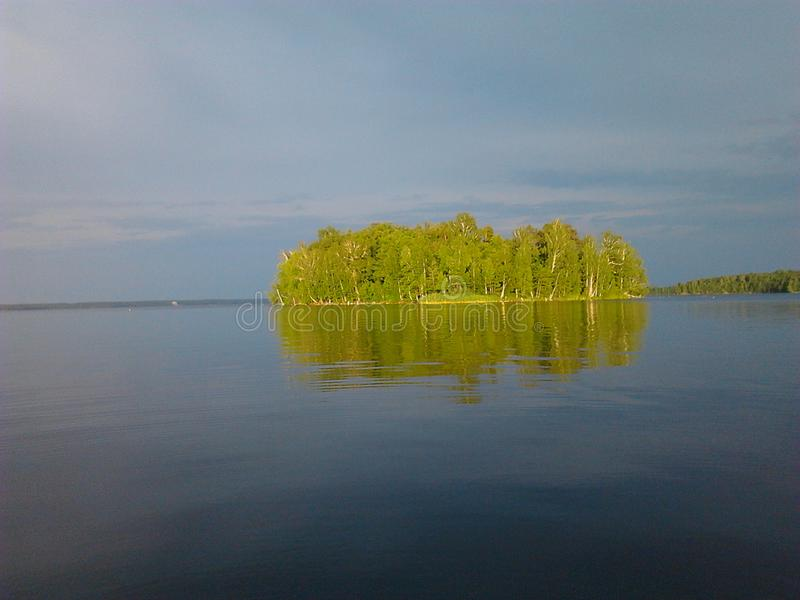 A lonely island in a big lake. A contrast of bright green and dark blue royalty free stock image