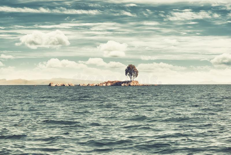 Lonely island on the lake. View of the Titicaca Lake on the border of Peru and Bolivia. Vintage filter applied. royalty free stock image