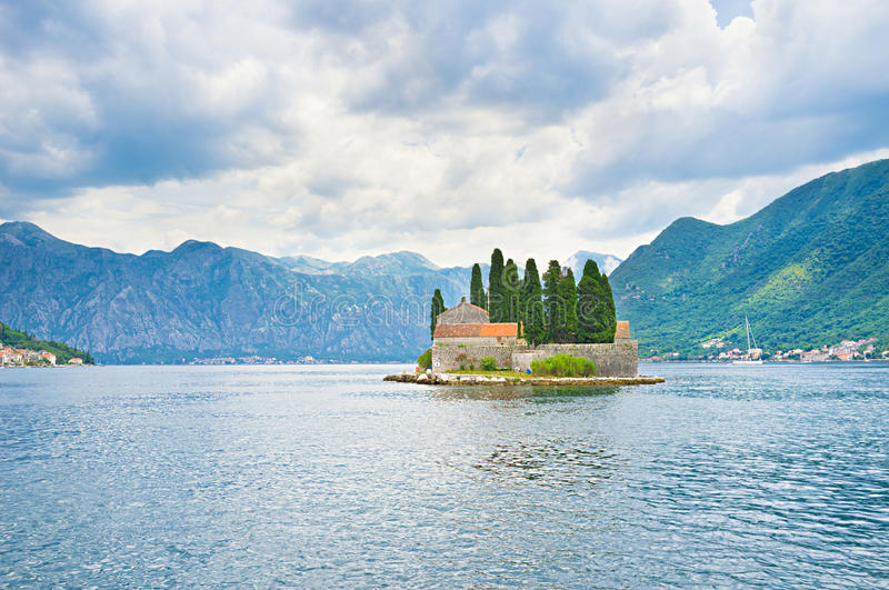 The lonely islet. The Benedictine monastery on St George islet is closed for tourist visiting, but the boats sail around it, Perast, Montenegro royalty free stock photography