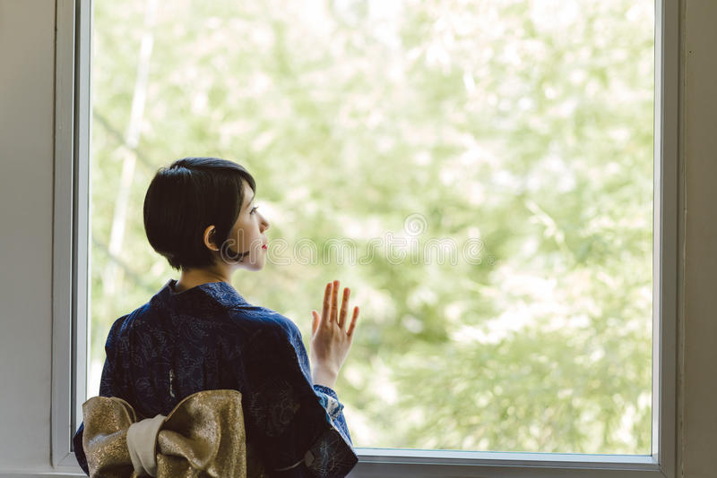 Lonely Japanese woman. In beautiful kimono looking through the window, rear view royalty free stock photos