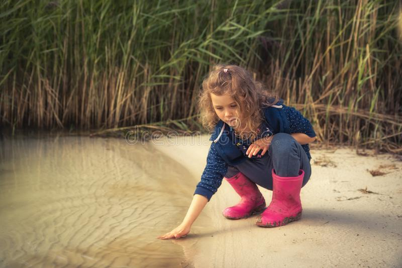 Lonely kid girl touching water on river bank in countryside concept childhood in countryside rustic lifestyle. Lonely kid girl touching water on river bank in royalty free stock image