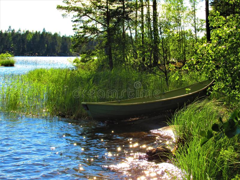 View of a lonely lake beach with green boat royalty free stock image