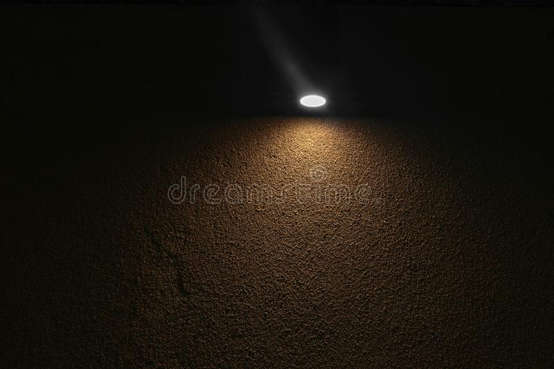 Lonely lamp illuminating brown concrete wall in absolute darkness.  stock image