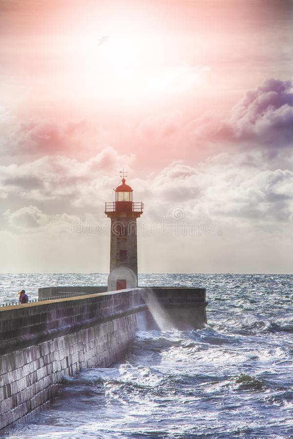 Lonely Lighthouse on the Pier in Porto City in Portugal Against Roaring Ocean stock photos