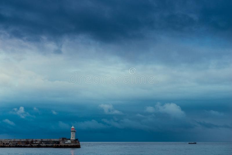 Lonely lighthouse with a red lantern on a background of rainy blue clouds. Over the sea stock photography