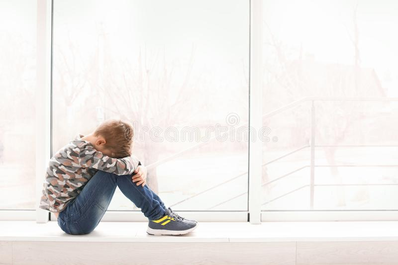 Lonely little boy near window indoors Child autism royalty free stock photo