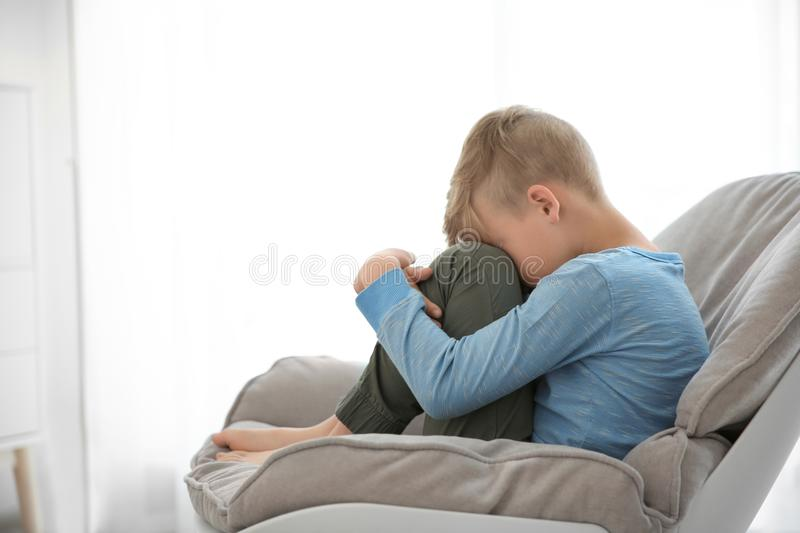 Lonely little boy sitting on chair at home royalty free stock photo