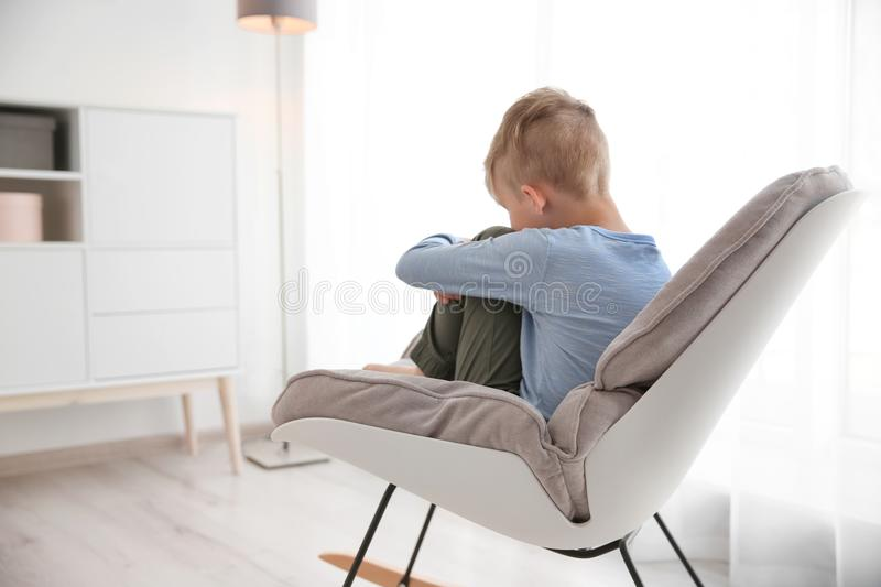 Lonely little boy sitting on chair at home royalty free stock image