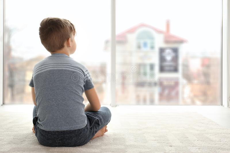 Lonely little boy sitting on floor in room royalty free stock photos