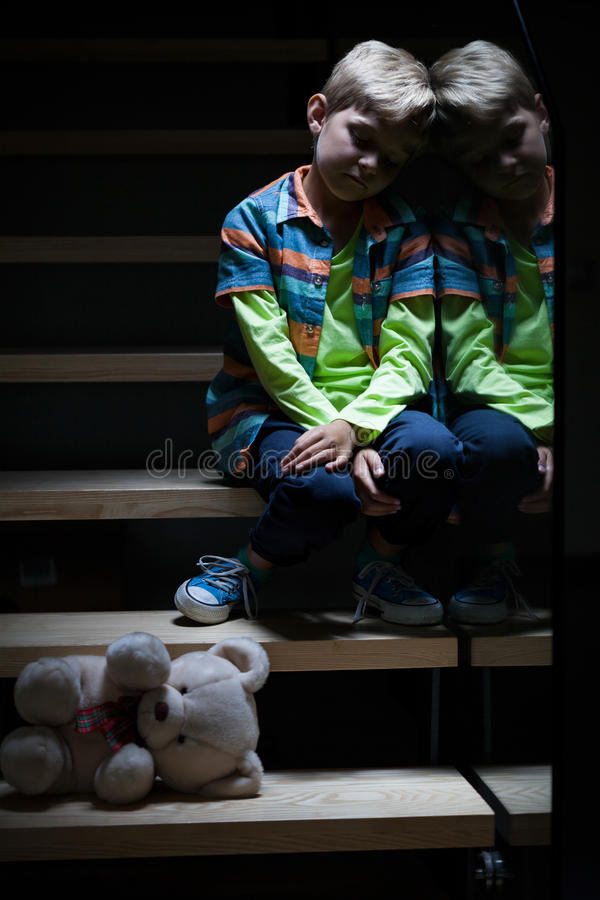 Lonely little boy on stairs royalty free stock photo