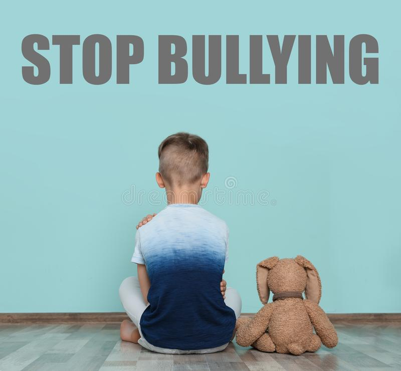 Lonely little boy with toy sitting on floor near wall. Message STOP BULLYING. Lonely little boy with toy sitting on floor near color wall. Message STOP BULLYING royalty free stock photos