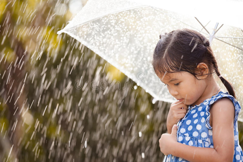 Lonely little girl with umbrella in rain. Lonely asian little girl with umbrella in rain stock photos