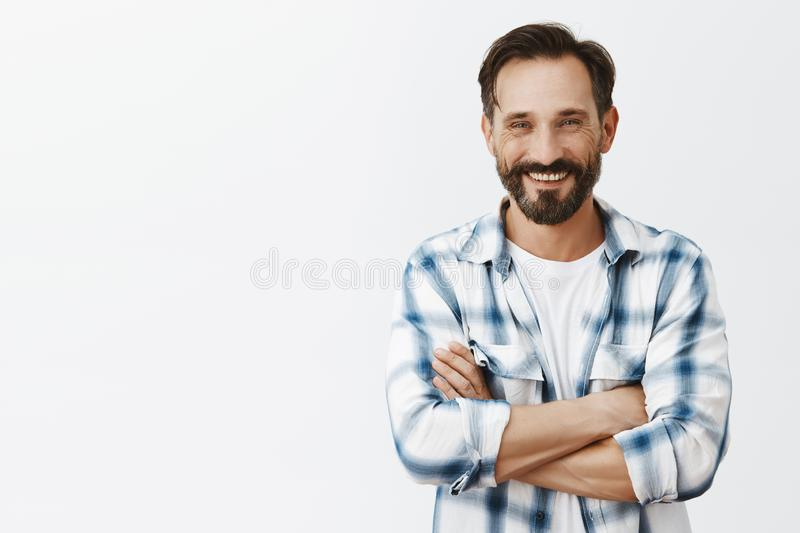 Lonely male farmer seeking woman to merry her, posting picture in social media. Portrait of happy handsome man with. Beard and moustache holding hands crossed royalty free stock image