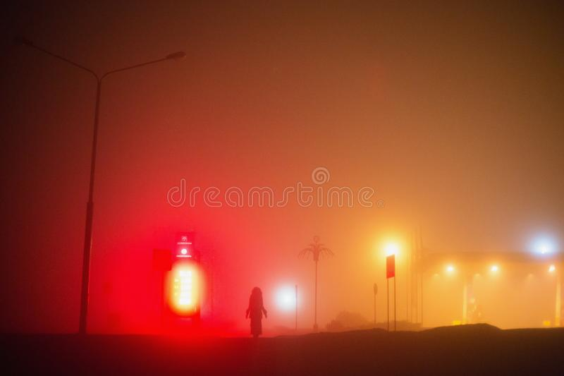 Lonely man. City at night in dense fog. Thick smog on a dark street. stock image