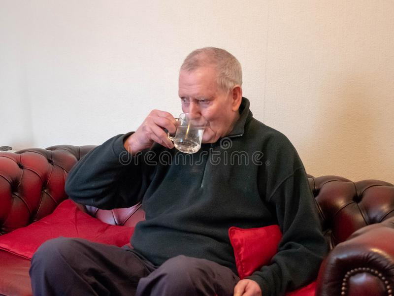 Lonely man drinking water on sofa stock photos