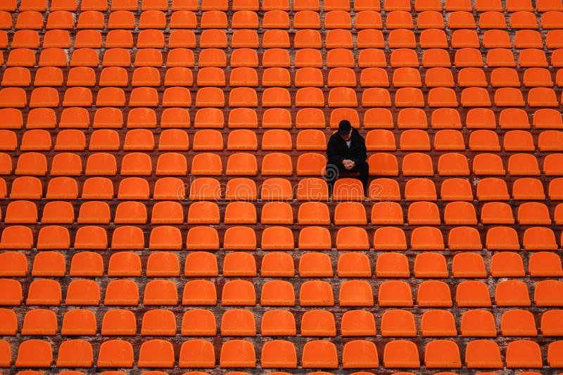 Lonely man on the empty stadium seat cheering for the team, one man army concept. Arena, fan, football, game, people, soccer, sport, cheerful, emotion, fun royalty free stock image