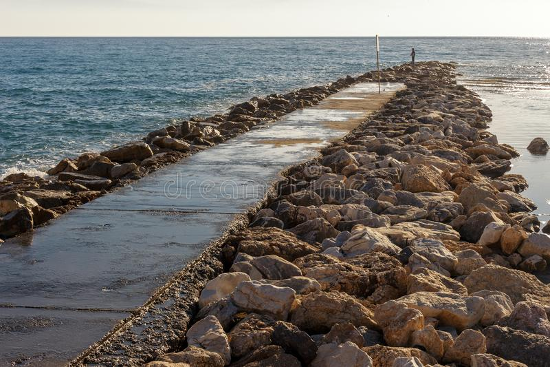 Lonely man fishing on the rocks royalty free stock photo