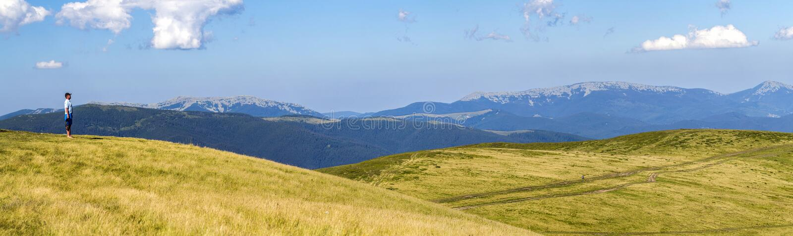 Lonely man hiker standing on a wide hill enjoing mountain view royalty free stock photography