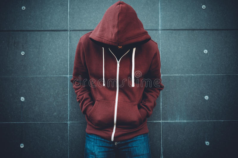 Lonely Man Leaning against an urban wall. Black stock image