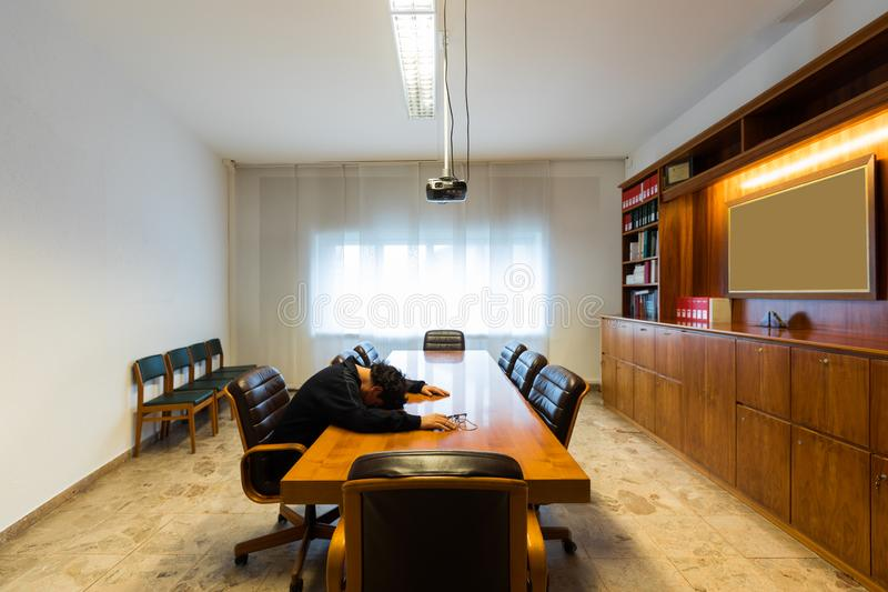 Lonely man in the meeting room is sleeping royalty free stock photo