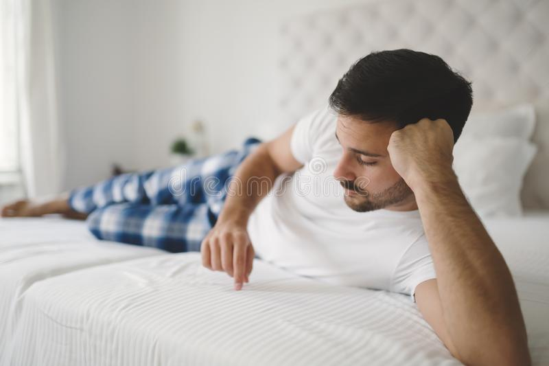 Lonely man in pajamas. Heartbroken lonely man in pajamas on bed stock photography
