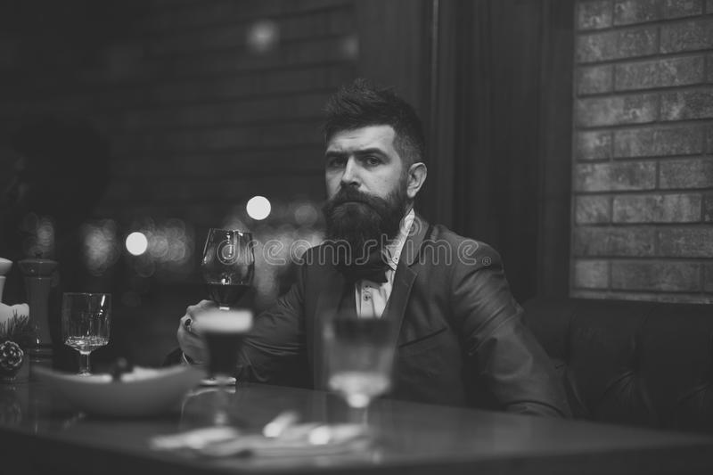 Lonely man in a restaurant. Date meeting of hipster awaiting in pub. Perfect wine. Businessman with long beard drink in stock photo