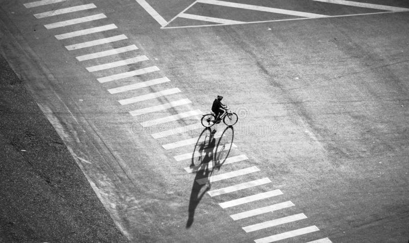 Lonely man ride bicycle on street with long shadow royalty free stock photo
