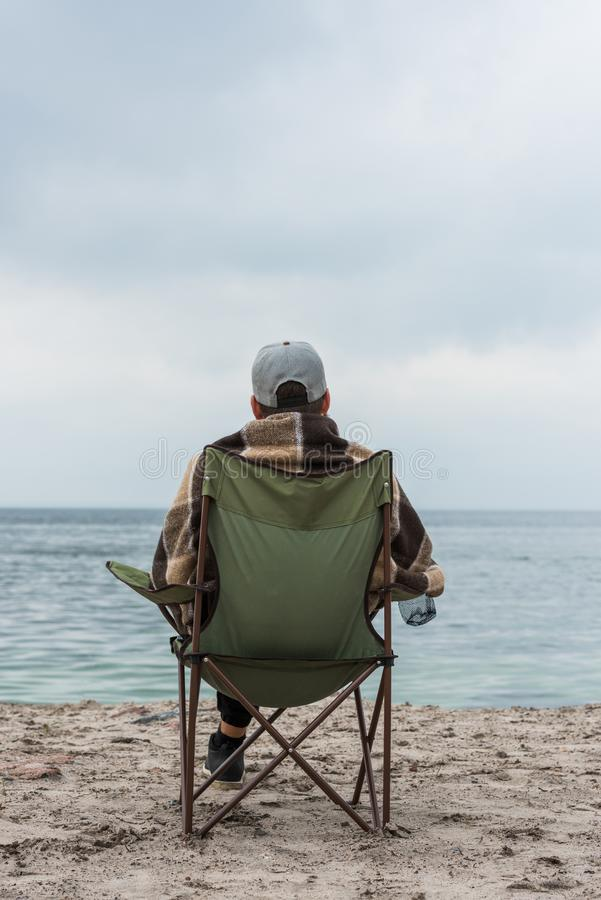 Lonely man sitting on chair at seashore on cloudy. Autumn day stock image