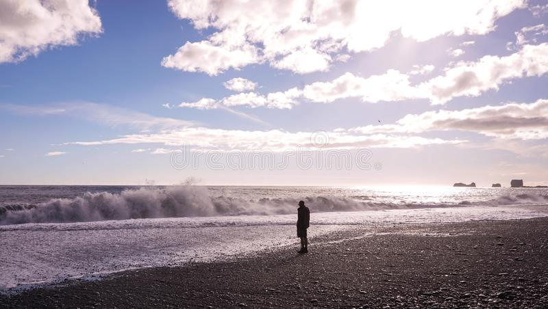 A lonely man standing at the beach royalty free stock photography