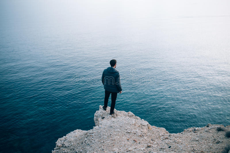 Lonely man stares at the sea. Silhouette of a young traveller and adventurer standing on a cliff staring into the deep dark water with a soft shadow gradient stock image