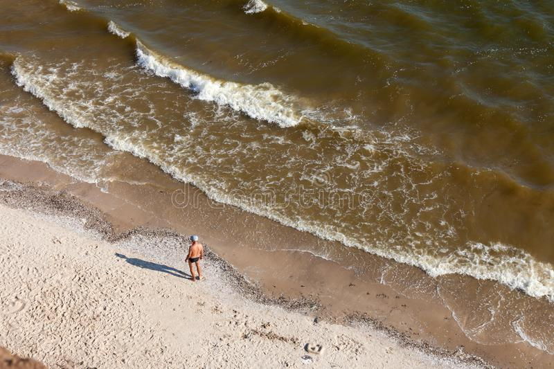 Lonely man strolls along a deserted beach alone. Early morning royalty free stock photography